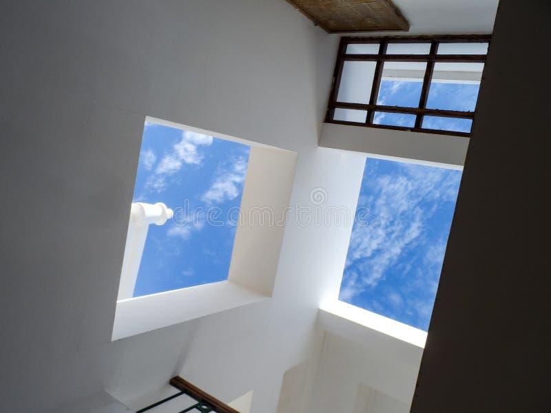 Ściany z okno z jaskrawym niebieskim niebem obrazy stock