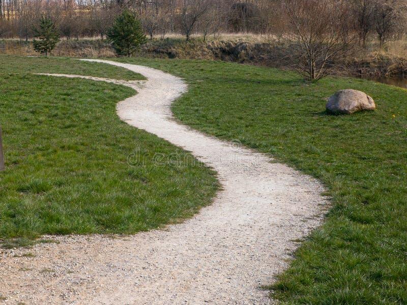 Ścieżka wzdłuż rzeki wiosną, skręcająca w lewo obraz stock