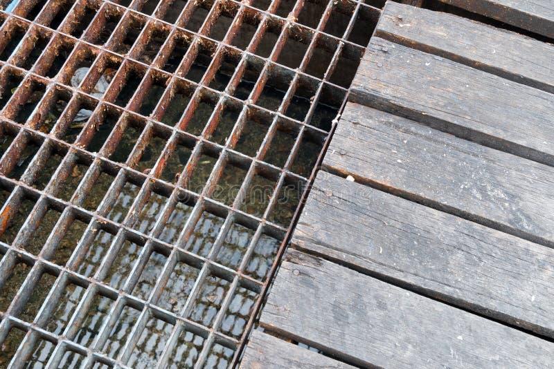 Ściekowa ośniedziała stali i drewna pokrywa nawadnia drenaż Tekstura i bac zdjęcia stock