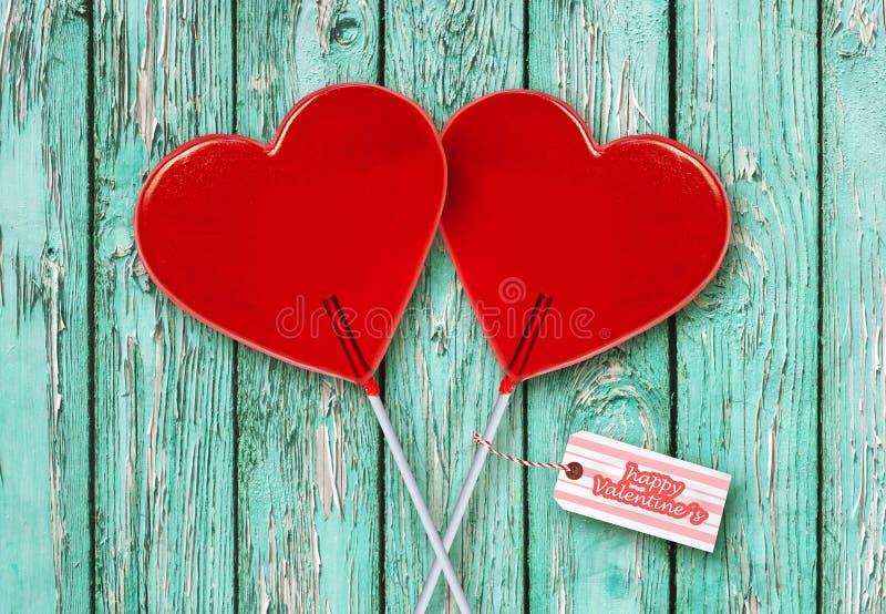 Ściennego papieru walentynek dnia kartka z pozdrowieniami z parą czerwoni kierowi kształtów lizaki wpólnie odizolowywający na roc zdjęcie royalty free