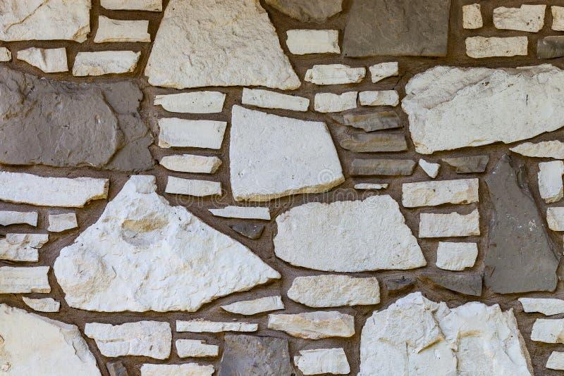 Ścienny tło z nieregularnymi sklejonymi białymi i brown kamieniami fotografia royalty free