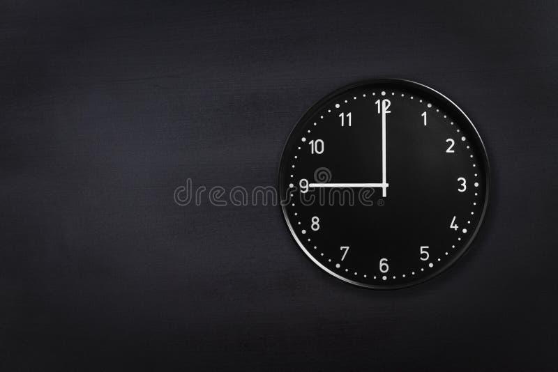 Ścienny zegar pokazuje dziewięć godzin na czarnym chalkboard tle Biuro zegar pokazuje 9am lub 9pm na czarnej teksturze obrazy royalty free