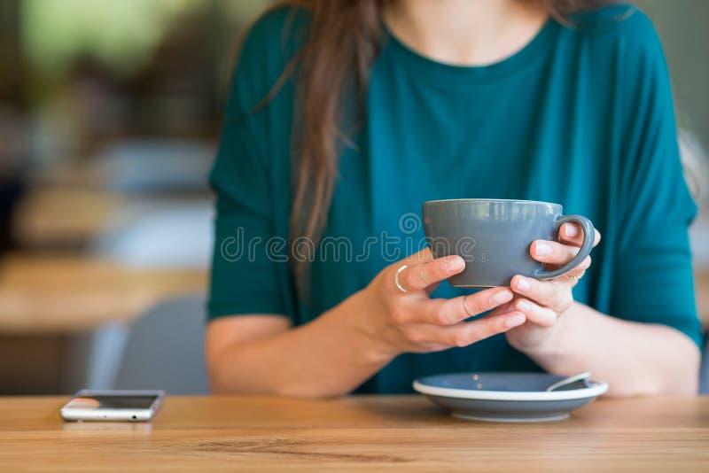 ścinku zbliżenia kawa zawiera filiżanki kartoteki ścieżkę Młoda kobieta w plenerowej kawiarni zdjęcia stock