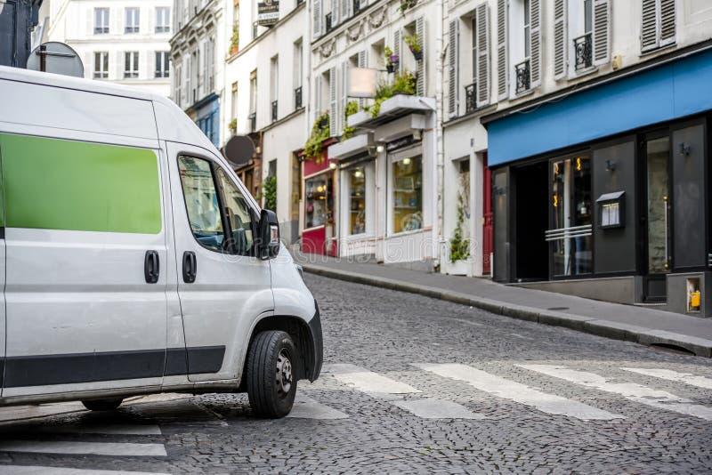 Ścisły oszczędnościowy mini samochód dostawczy dla małego biznesu i miejscowego dostawy obraca dalej rozdroże na miasto ulicie zdjęcie stock