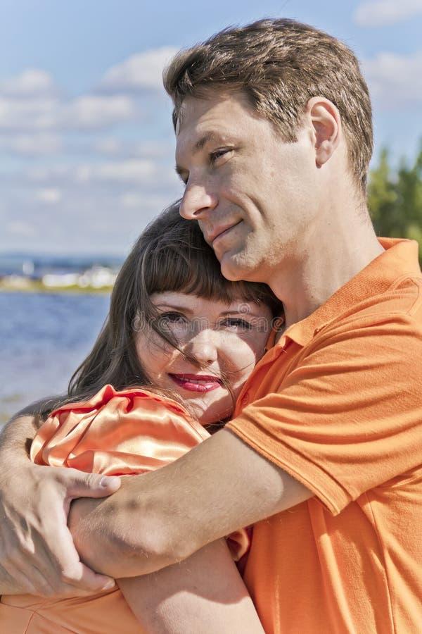 Ściskać mężczyzna i kobiety w pomarańcz ubraniach fotografia stock