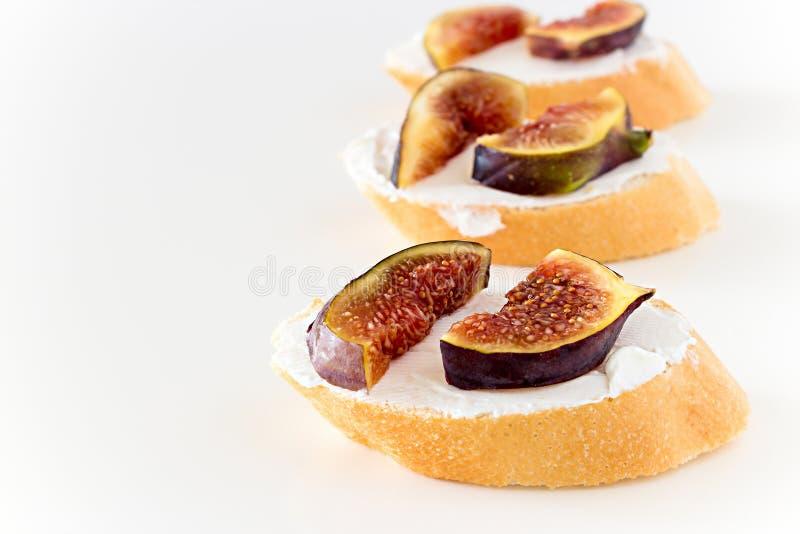 Ściska Bruschetta z figą i Koźlim serem na białym tle zdjęcie royalty free