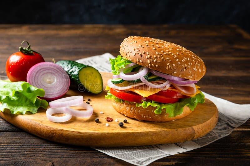 Ściska hamburger z baleronem, serem i warzywami na drewnianej desce z składnikami, kosmos kopii Fast food dla śniadania lub lunch fotografia stock