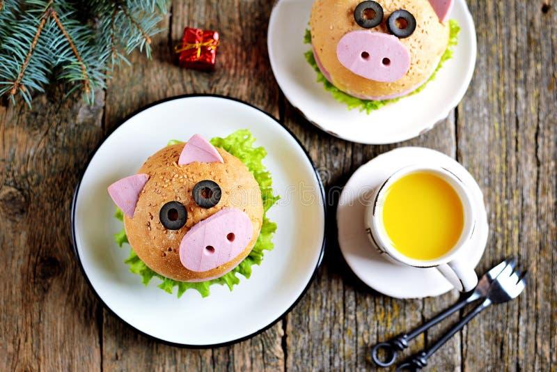 Ściska z baleronem, serem i sałatą, w postaci ślicznej świni - symbol 2019 Dziecka śniadaniowy Bożenarodzeniowy tło wierzchołek v obrazy royalty free