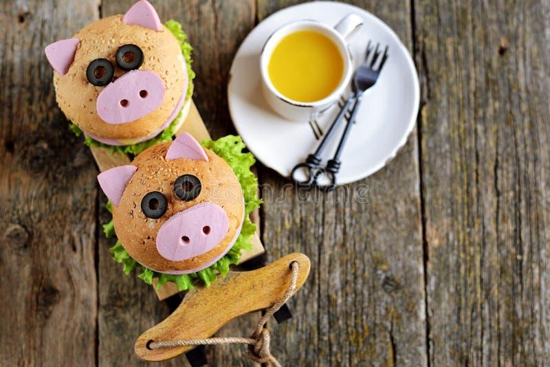 Ściska z baleronem, serem i sałatą, w postaci ślicznej świni - symbol 2019 Dziecka śniadaniowy Bożenarodzeniowy tło wierzchołek v zdjęcie stock