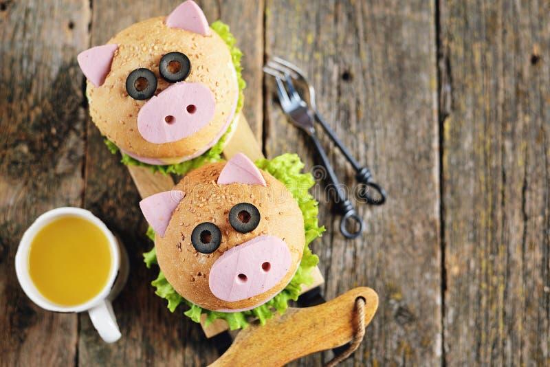 Ściska z baleronem, serem i sałatą, w postaci ślicznej świni - symbol 2019 Dziecka śniadaniowy Bożenarodzeniowy tło wierzchołek v fotografia royalty free