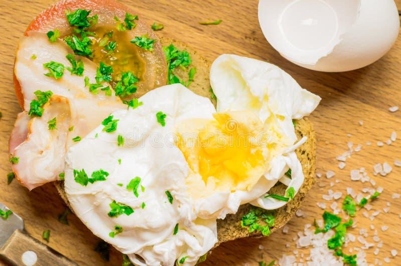 Ściska z bekonem, pomidorem i kłusującym jajkiem, zdjęcie stock