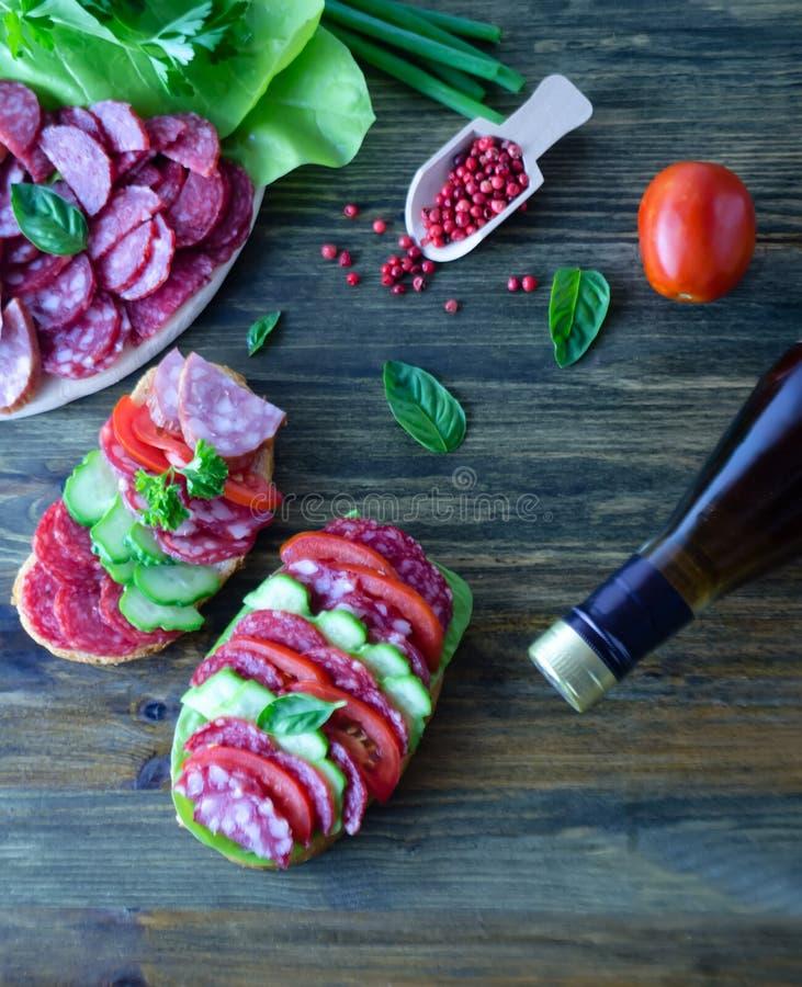 Ściska z salami z pomidorami i ogórkami następnie pokrajać basilów liście z, salami i pomidor sałatką i butelką wino i zdjęcie royalty free