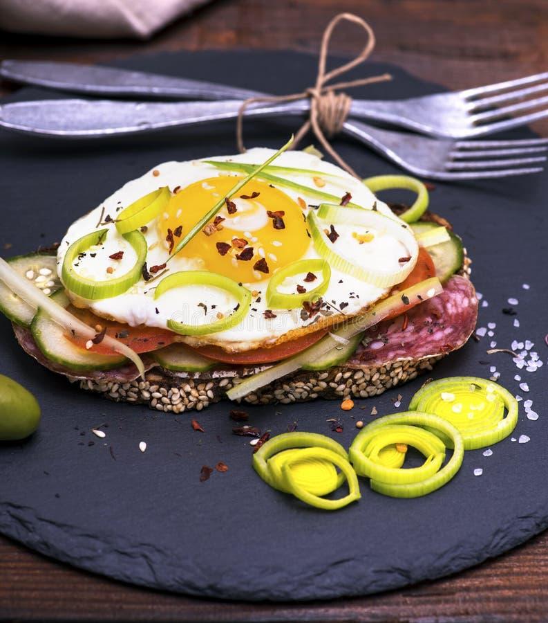 Ściska z smażącym jajkiem, kiełbasianym salami i warzywami, fotografia royalty free