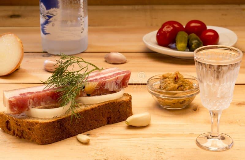 Ściska z spiced okrasą słuzyć z czosnkiem, cebulami, musztardą, zalewami, pomidorami i zimną ajerówką, obrazy royalty free