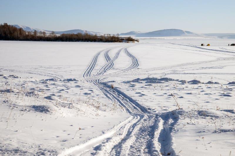 Ślad od snowmobile na śnieżnym jeziorze z rybakami w tle zdjęcia stock