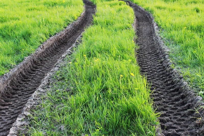 ślada maszyny ciężkie ciągnik w piasku na lato luksusowej zielonej trawie zdjęcie royalty free