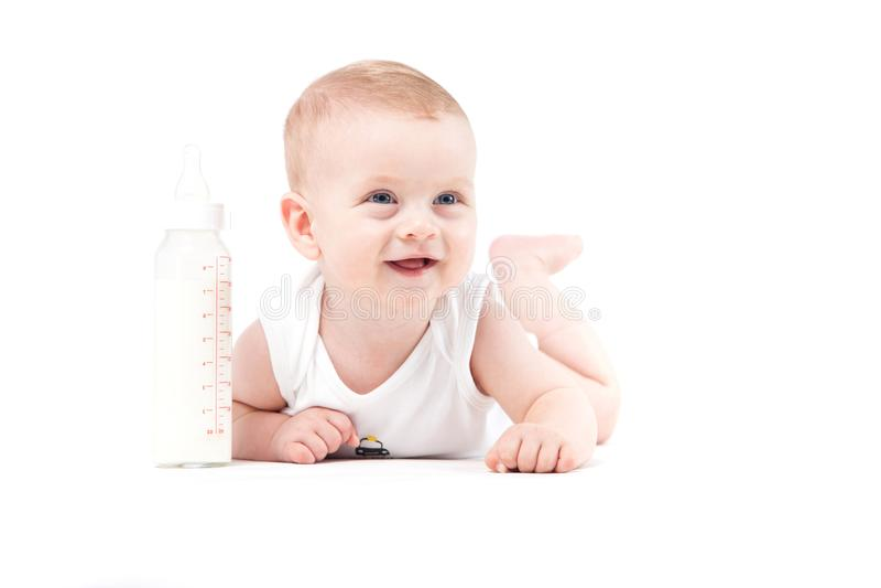 Śliczna ładna chłopiec w białej koszula kłama na brzuszku z dojnym bott zdjęcie royalty free