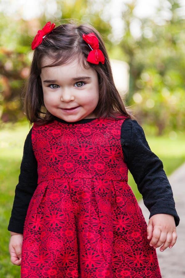 Śliczna, ładna, szczęśliwa, uśmiechnięta berbeć dziewczynka z niegrzecznym figlarnie uśmiechem z elegancką czerwieni i czerni suk fotografia royalty free