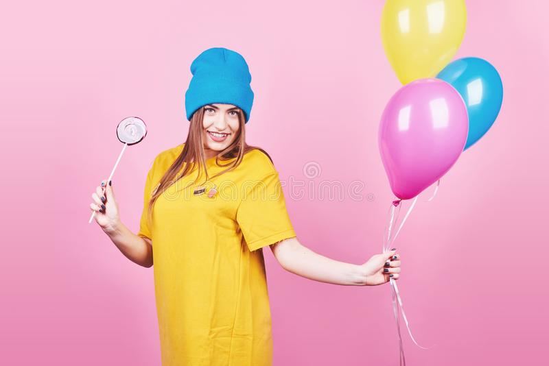 Śliczna śmieszna dziewczyna ono uśmiecha się na różowym tle w błękitnej nakrętki portrecie trzyma lotniczych kolorowych balony i  zdjęcia royalty free