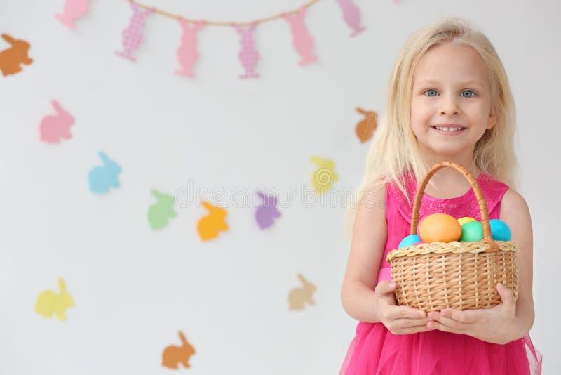 Śliczna śmieszna dziewczyna z koszykowy pełnym Wielkanocni jajka obrazy royalty free