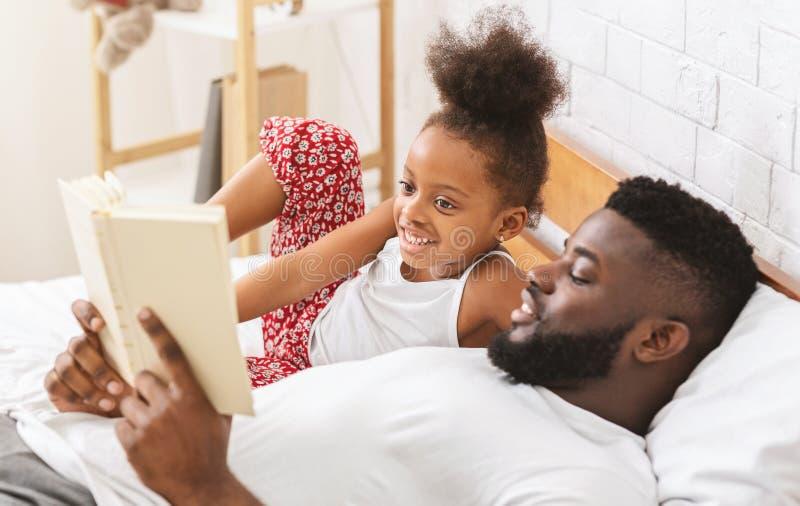 Śliczna afrykańska dziewczyna słucha bajka, tata czytelnicza książka jego dziecko zdjęcie stock