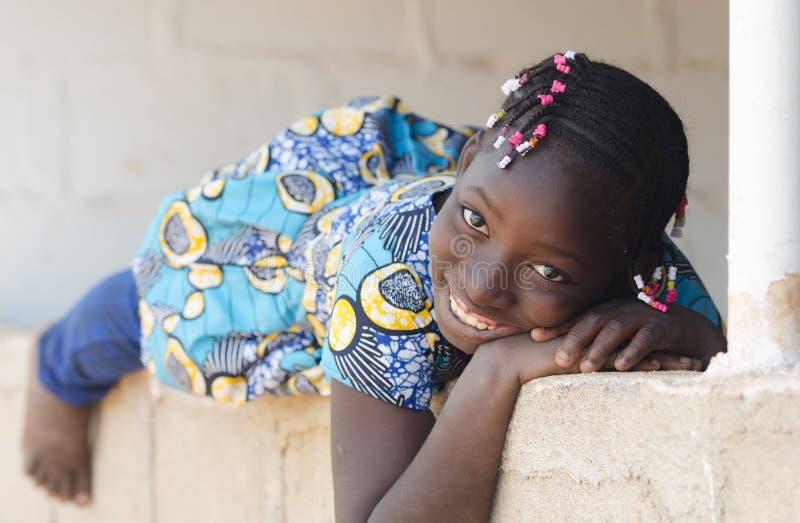 Śliczna Afrykańska pochodzenie etniczne dziewczyna Kłaść Outdoors Śmiać się i ono Uśmiecha się fotografia stock