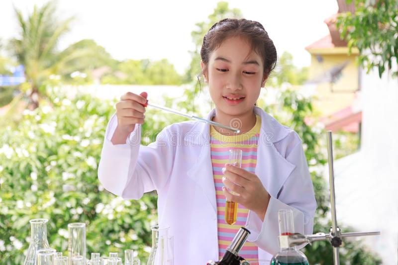 Śliczna Azjatycka dziewczyna w nauka munduru studiowania substancji chemicznej obrazy royalty free