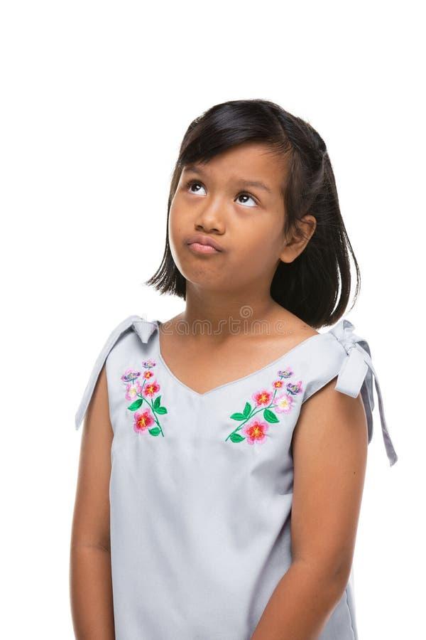 Śliczna azjatykcia ciemna mała dziewczynka robi śmiesznej emocji na twarzy zdjęcie royalty free