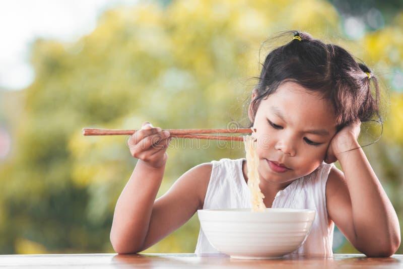 Śliczna azjatykcia dziecko dziewczyna zanudzająca jeść Natychmiastowych kluski obraz stock