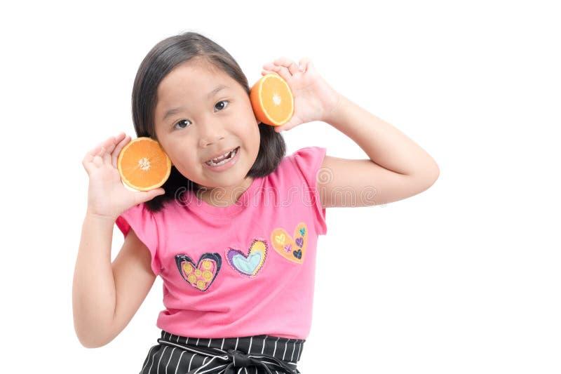 Śliczna azjatykcia dziewczyna bawić się z świeżymi mandarynek owoc fotografia stock