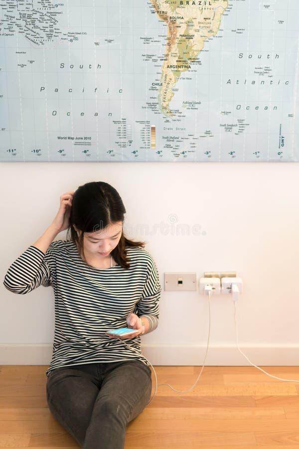 Śliczna azjatykcia dziewczyna udaremnia z telefon baterią, ładuje na ścianie obrazy royalty free