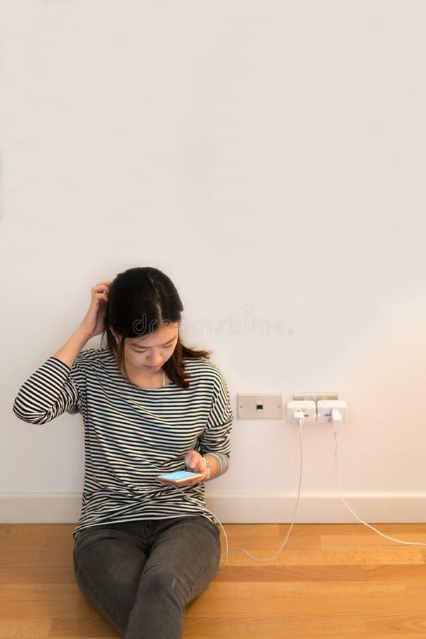 Śliczna azjatykcia dziewczyna udaremnia z telefonem, ładuje bateria z kopii przestrzenią, obrazy royalty free