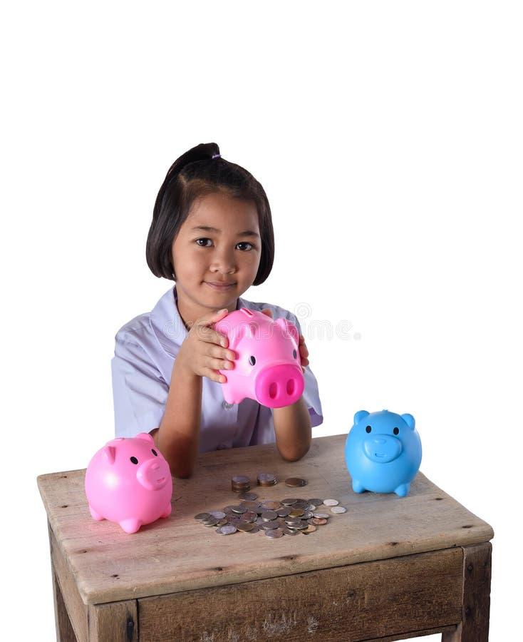 Śliczna azjatykcia dziewczyna zabawę z wiele prosiątko bank odizolowywający na bielu zdjęcia stock