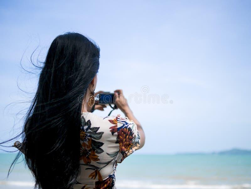 Śliczna azjatykcia kobieta jest ubranym retro smokingową pozycję przy nadmorski mienia kamerą w ręce i bierze fotografię fotografia royalty free