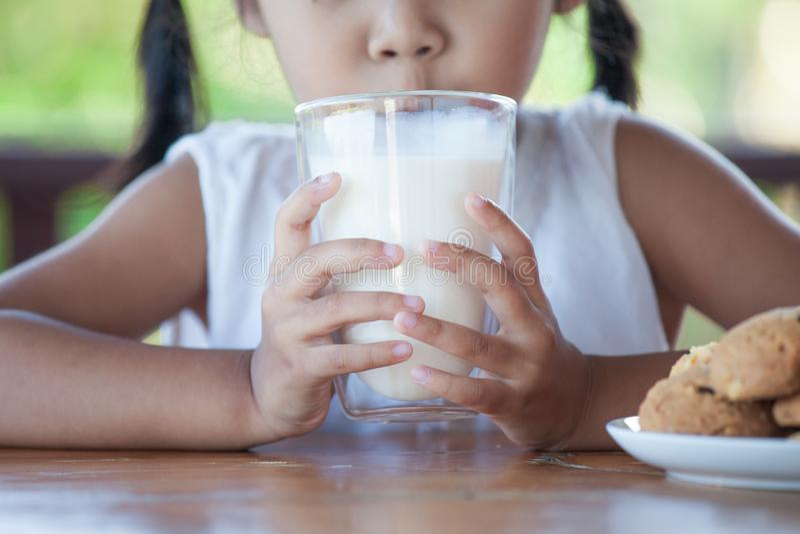 Śliczna azjatykcia małe dziecko dziewczyna pije mleko od szkła fotografia royalty free