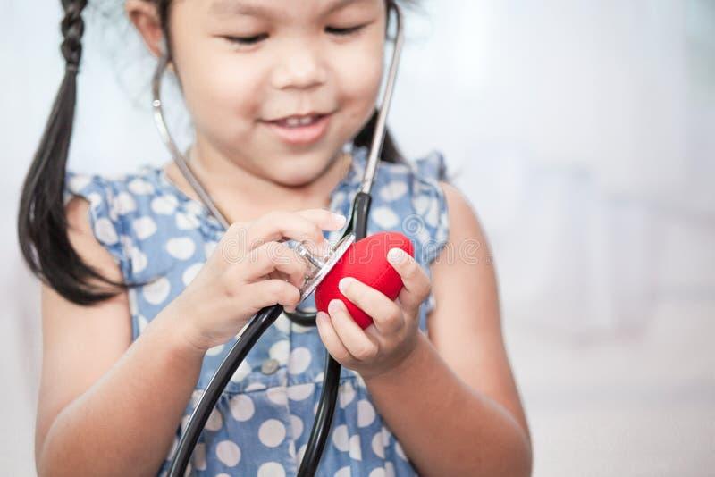 Śliczna azjatykcia małe dziecko dziewczyna z stetoskopem bawić się lekarkę zdjęcia royalty free