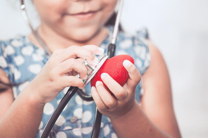 Śliczna azjatykcia małe dziecko dziewczyna z stetoskopem bawić się lekarkę obraz stock