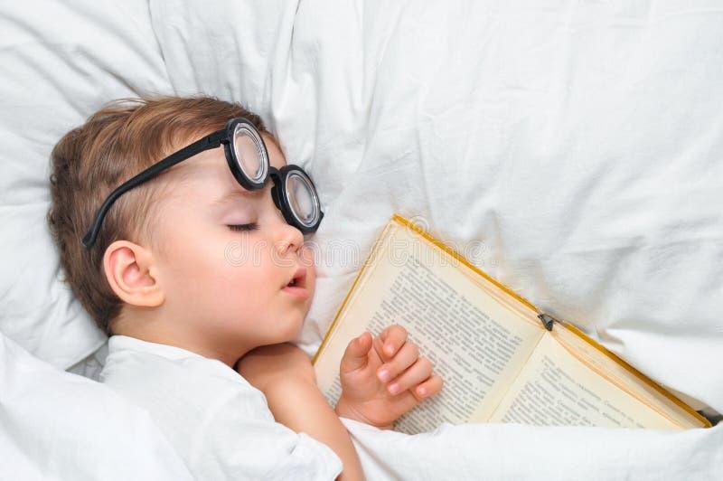 Śliczna berbeć chłopiec śpi w round szkłach z starą książką pod białą koc zdjęcie royalty free