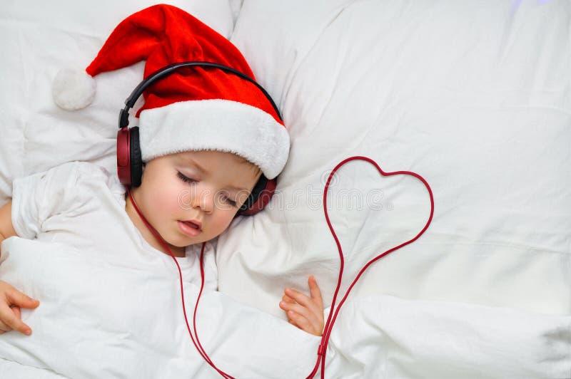 Śliczna berbeć chłopiec śpi w Santa hełmofonach i blisko drutowania w postaci serca kapeluszowych i czerwonych zdjęcie royalty free