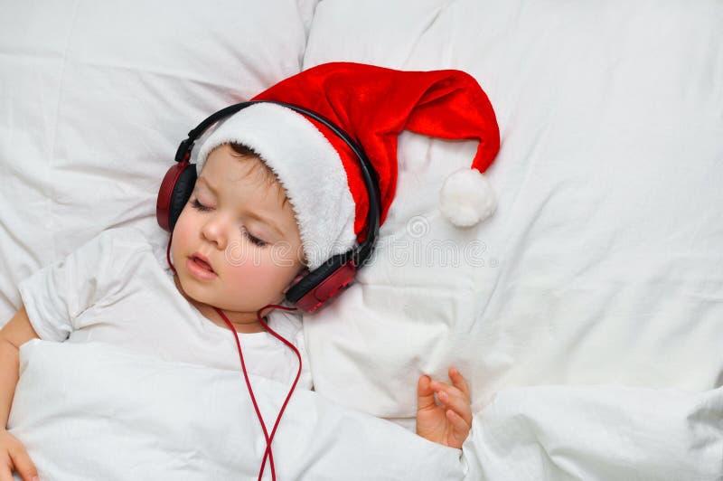 Śliczna berbeć chłopiec śpi w Santa kapeluszowych i czerwonych hełmofonach zdjęcia royalty free