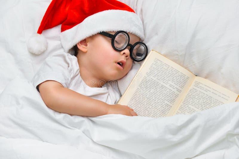 Śliczna berbeć chłopiec śpi w Santa kapeluszu i round szkłach z starą książką pod białą koc fotografia stock
