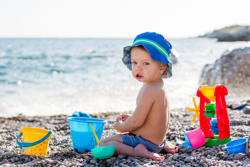 Śliczna berbeć chłopiec bawić się na plaży obraz royalty free