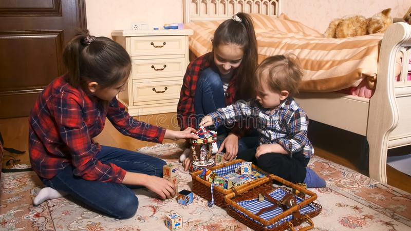 Śliczna berbeć chłopiec bawić się z zabawkami z jego starymi siostrami fotografia stock