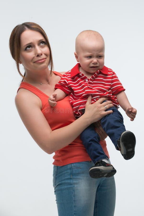 Śliczna berbeć chłopiec jest niegrzeczna na mom€™s rękach zdjęcie royalty free