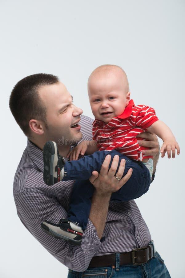 Śliczna berbeć chłopiec jest niegrzeczna na tata rękach zdjęcia stock