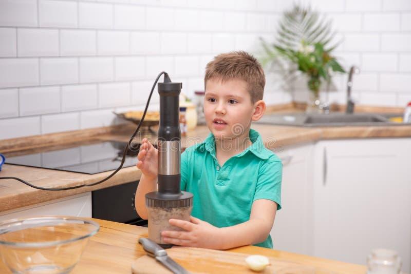 Śliczna berbeć chłopiec używa ręki blender robić minced mięsu Narządzanie posiłek w kuchni obraz stock