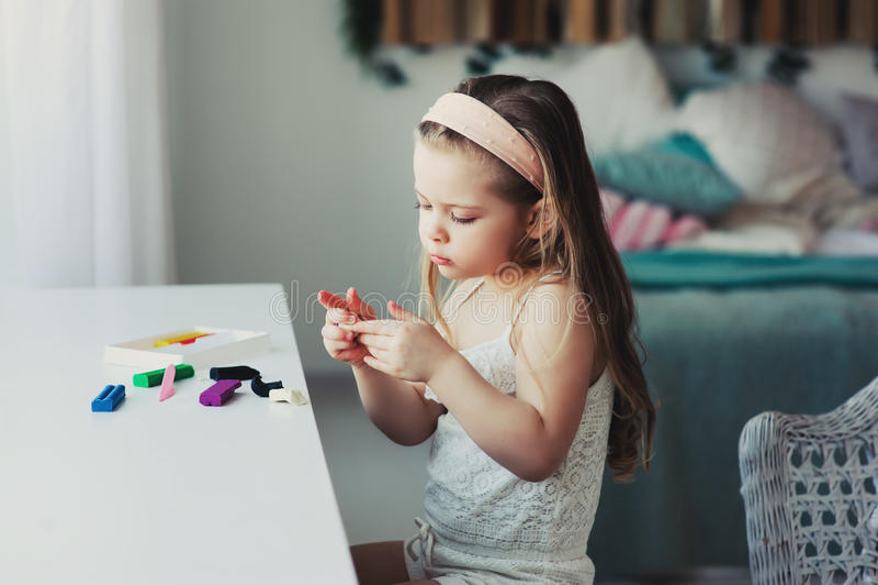 Śliczna berbeć dziewczyna bawić się z plasteliną lub sztuki ciastem w domu fotografia royalty free