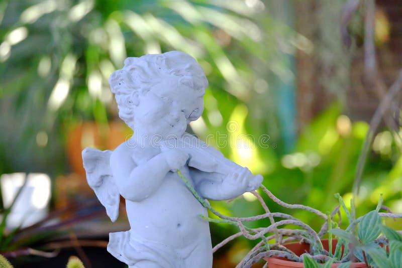 Śliczna biała amorek rzeźba bawić się skrzypce i gapi się w zielonym ogródzie zdjęcie royalty free