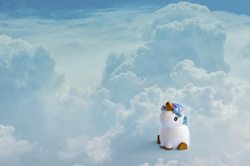 Śliczna biała jednorożec na bławym pastelu chmurnieje Dziecko prysznic, dziewczyna urodziny poj?cie (Indonezja) Horyzontalny z ko zdjęcie stock