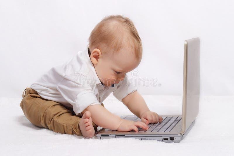 Śliczna blond chłopiec pracuje z laptopem zdjęcie royalty free